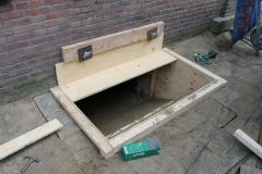 In de voorgevel wordt een uitsparing gemaakt om de uitgegraven grond af te voeren. Ook wordt hierdoor materiaal en machines onder de woningen gebracht.