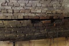 De bouwmuur rust op het langshout. Omdat het langshout is aangetast wordt het ondersteund om instorting te voorkomen.