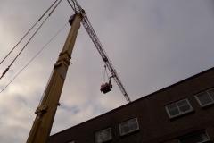 De heimachine wordt over de woningen getild door een torenkraan.