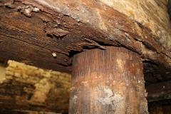 Het langshout (de horizontale balk die op de paalkoppen rust en de draagmuur draagt) is flink aangetast. De paal drukt er doorheen.